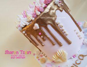 עוגת נטיפי זהב גבוהה ומרשימה עם נשיקות בגווני קרם וורוד.